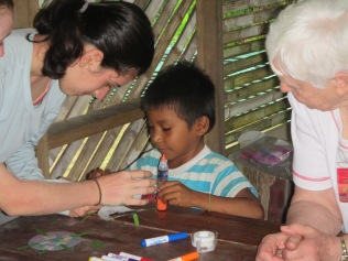 Ariana and Karon help Kiki and others make paper turtles while the adults learn about the village's charapa (Amazon River Turtle) Project